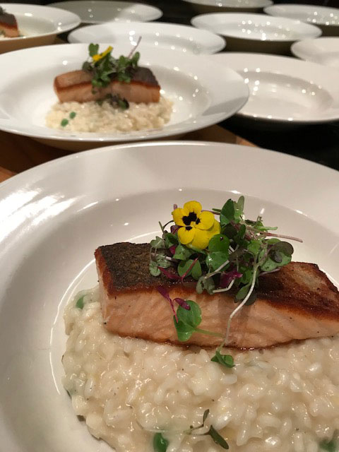 A close-up image of seared fish and risotto