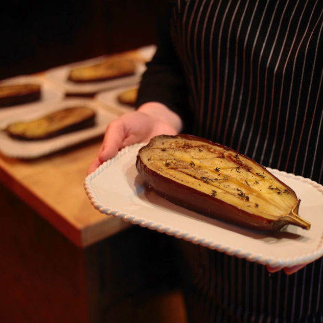 Roasted Eggplant on a plate being held by a figure