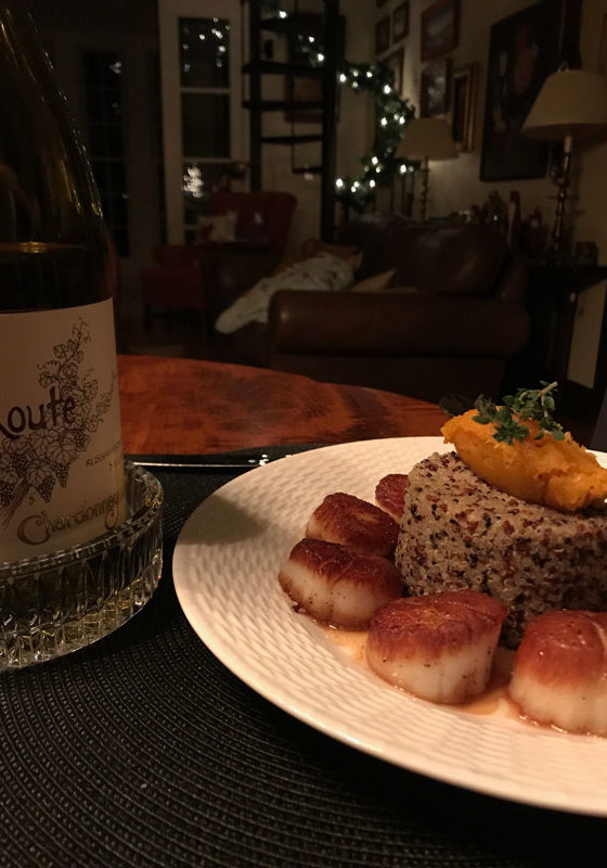 Scallops and risotto on a plate with a bottle on wine next to it