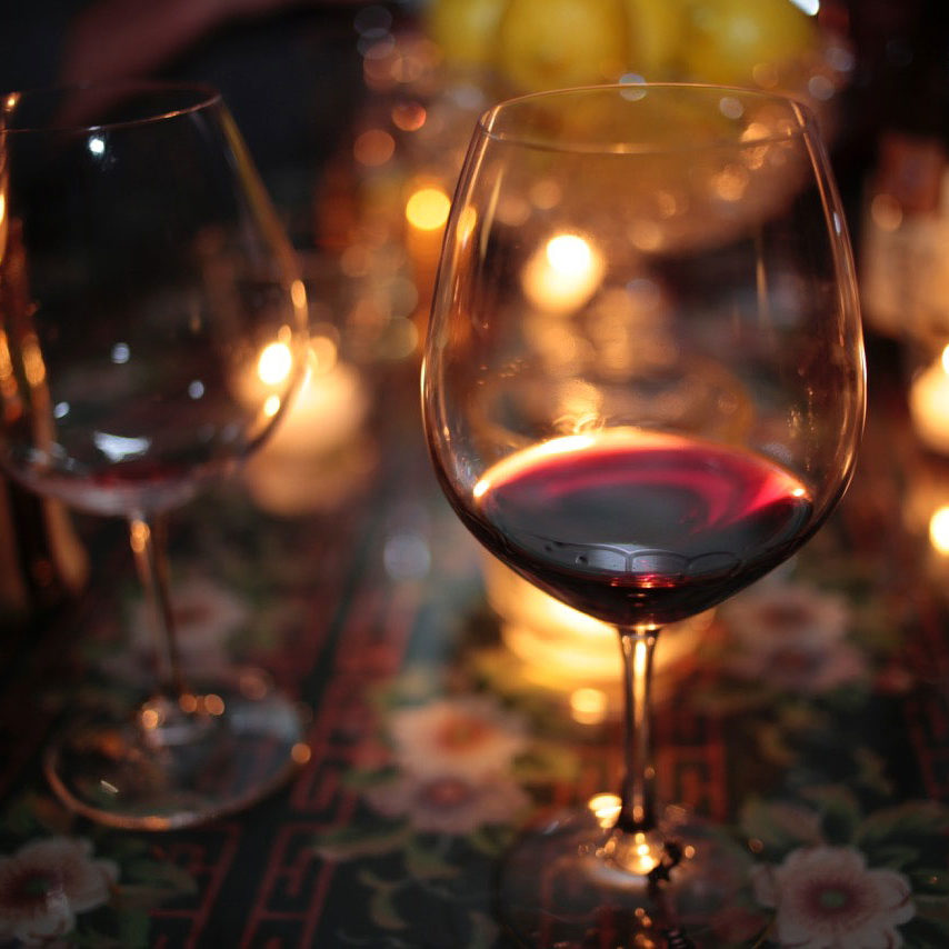 Wine glasses filled with red wine, with candles in the background, on a soft lit table